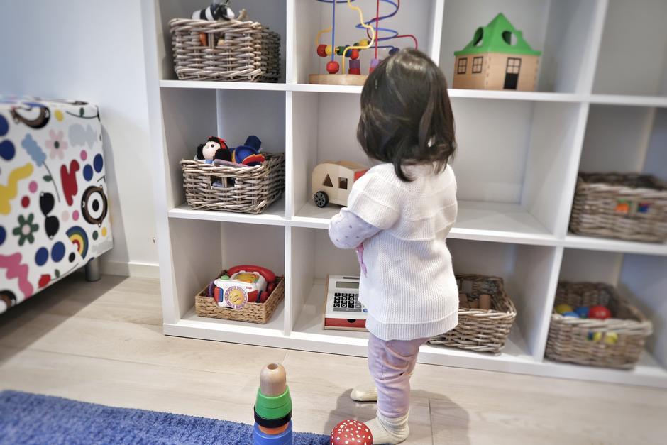 Barn med ryggen til ser mot hylle med leker.