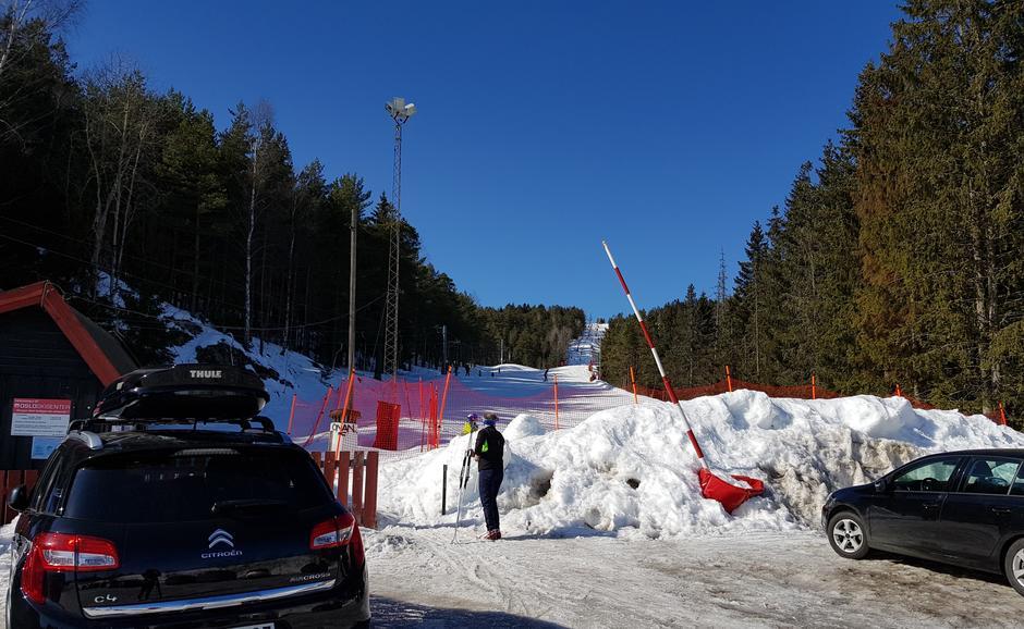 Parkeringsplass med to biler i forgrunnen. En person på vei mot alpinbakke. Alpinbakke i bakgrunnen.