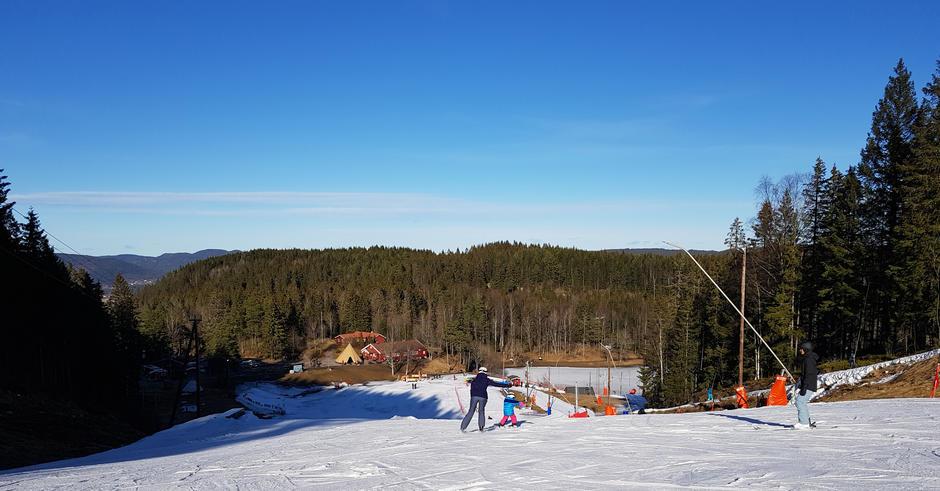 Alpinbakke sett fra toppen. To voksne og et barn står på ski
