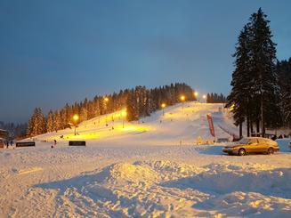 Alpinbakke om kvelden, sett mot toppen. Bil parkert i forgrunnen