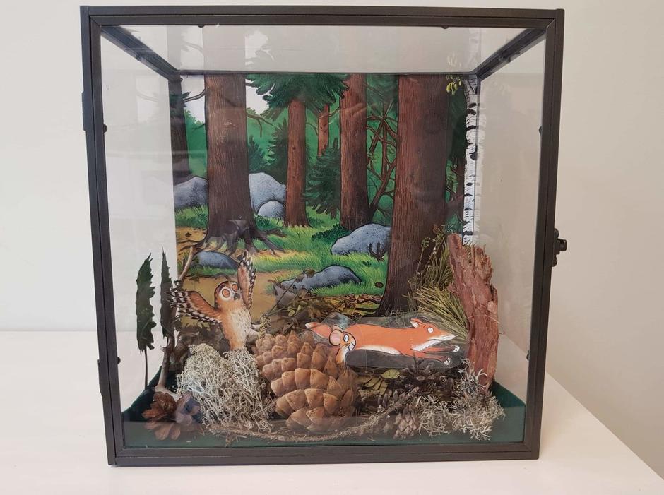 En firkantet glassmonter med kongler, lønn og andre naturmaterialer sammen med tegning av en skog med ugler og rever.