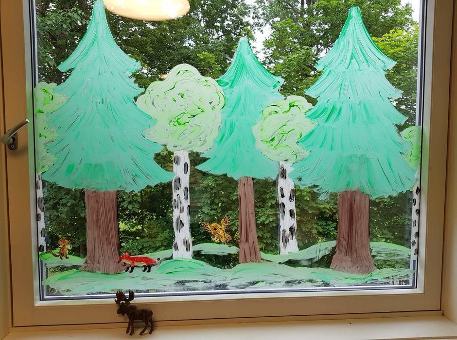 Trær og natur og en rev er malt nesten over hele vinduet.