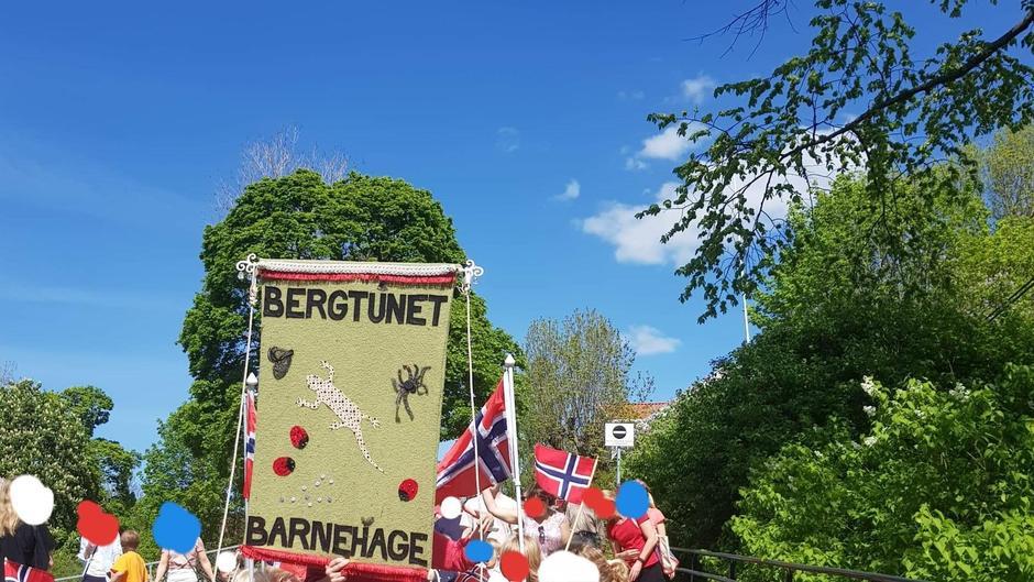 Barn og voksne går i tog med norske flagg og en fane med påskriften Bergtunet barnehage vises.