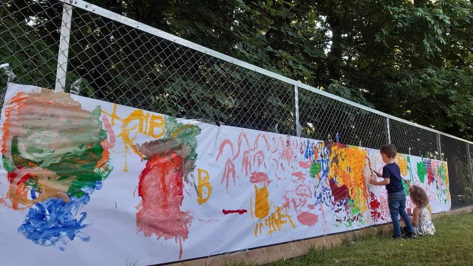 Nærbilde av et gjerde med duk med malingstegninger hengende, og to små barn står litt bortenfor og maler på den samme duken.