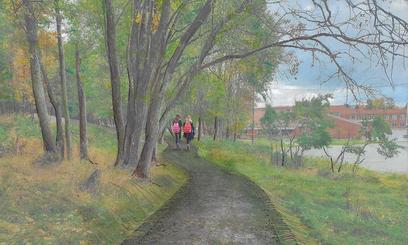 To jenter med skolesekk går langs en tursti. På den ene siden av tustien står høye trær, på den andre siden mindre trær mot en gressflate som grenser mot en skolegård og skolebygning.