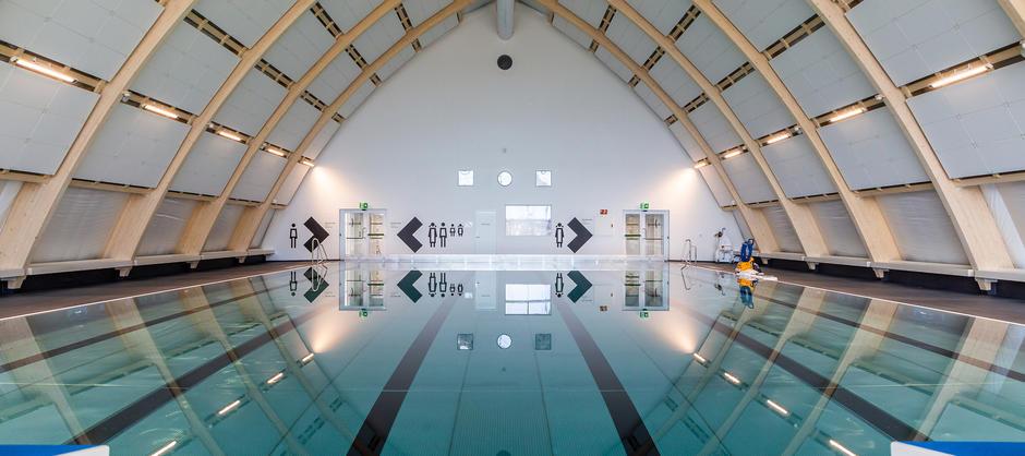 Bilde av svømmebassenget i Økern bad, med skilting til garderober og toalett i bakgrunnen.