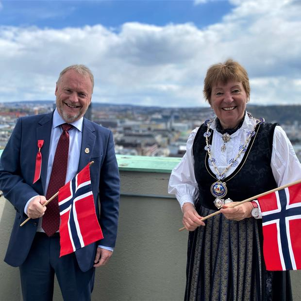 Byrådsleder Raymond Johansen og ordfører Marianne Borgen står ved siden av hverandre, kledd i bunad og dress, med flagg.