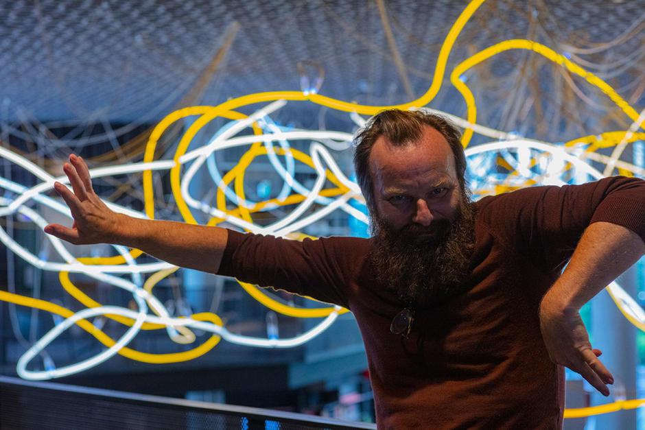 Kunstneren Lars Ramberg foran en lysinstallasjon av gule og hvite neonrør.