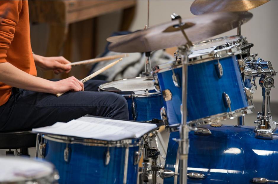 Trommesett hvor to ivrige hender med trommestikker som slår på trommene.