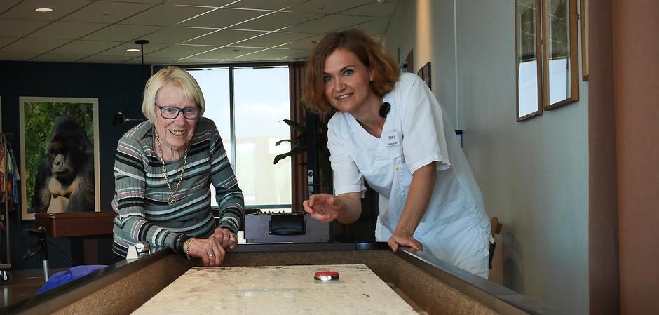 Beboer og ansatt spiller shuffleboard på Lindeberghjemmet