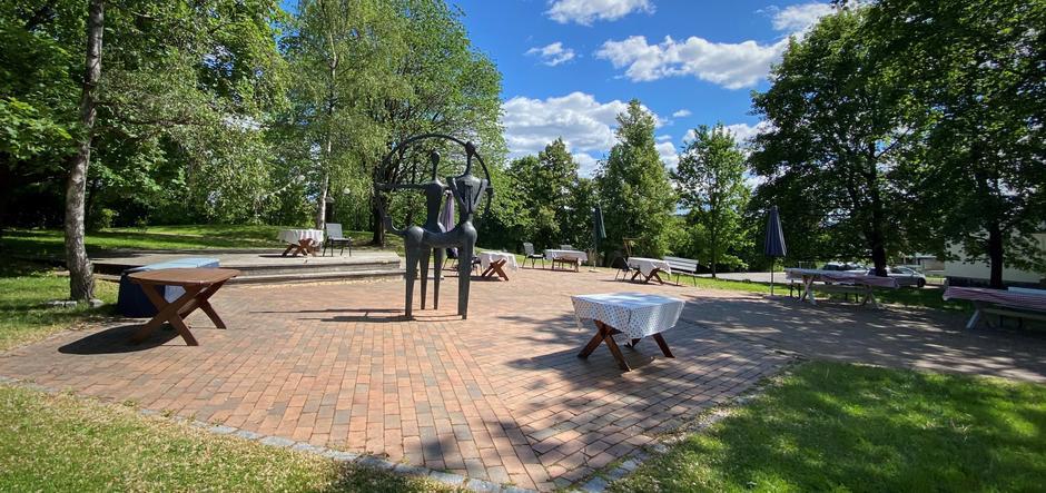 hage med bord og stoler, skulptur, trær og plen
