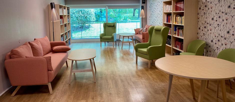 stue med sofaer, lenestoler, bord og bokhyller. stort vindu med utsikt mot hage