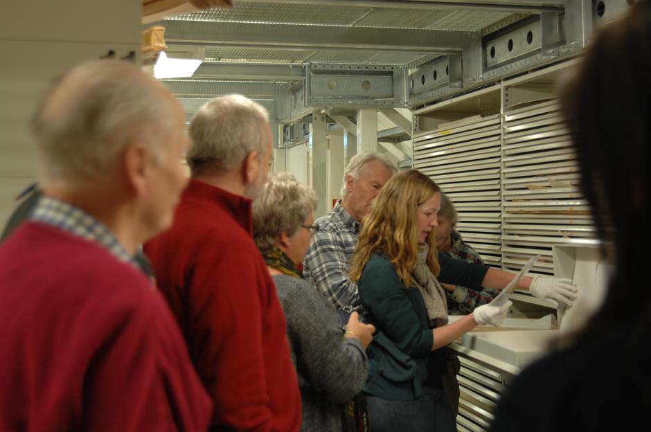 En gruppe mennesker står bøyd over et dokument holdt av en arkivar med hvite hansker på.