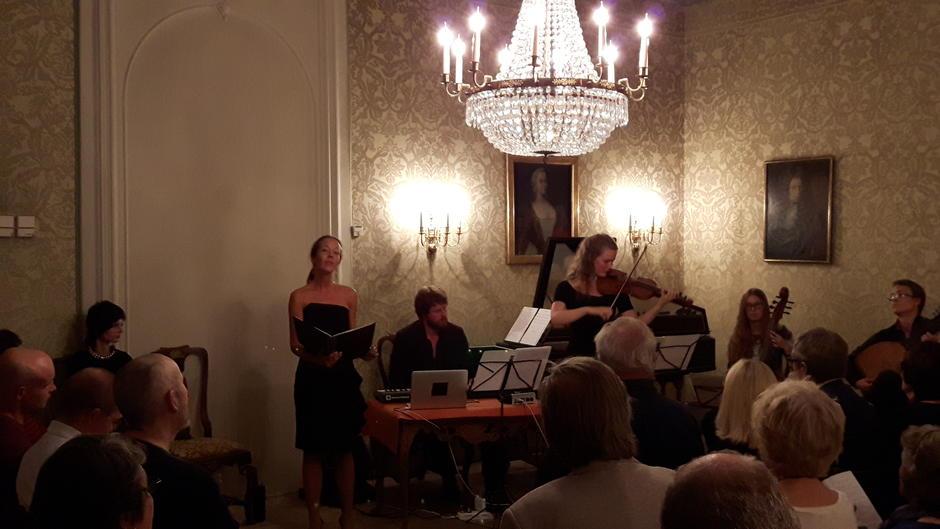 Sangerinne, pianist og fiolinist fremfører musikk i en dunkel belyst vakker sal med silketapeter i Oslo Ladegård.