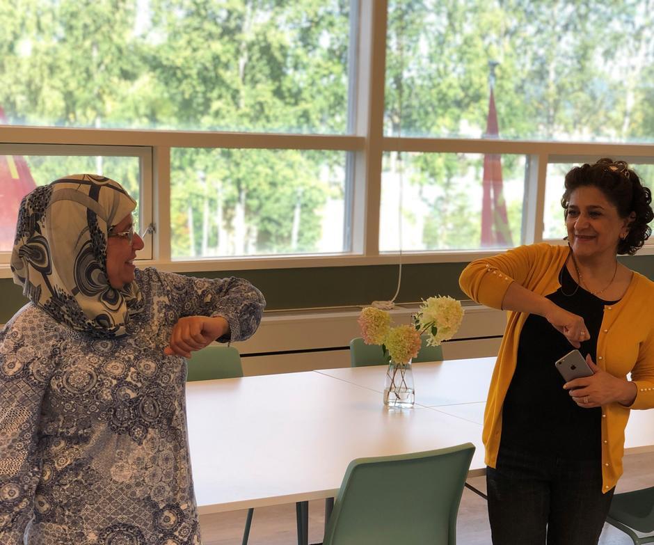 To kvinner som gjør korona-hilsen med albuen