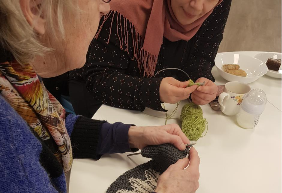Nærbilde av to kvinner som strikker
