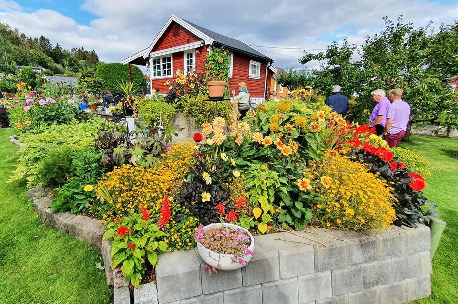Rødt hus med hage og blomster