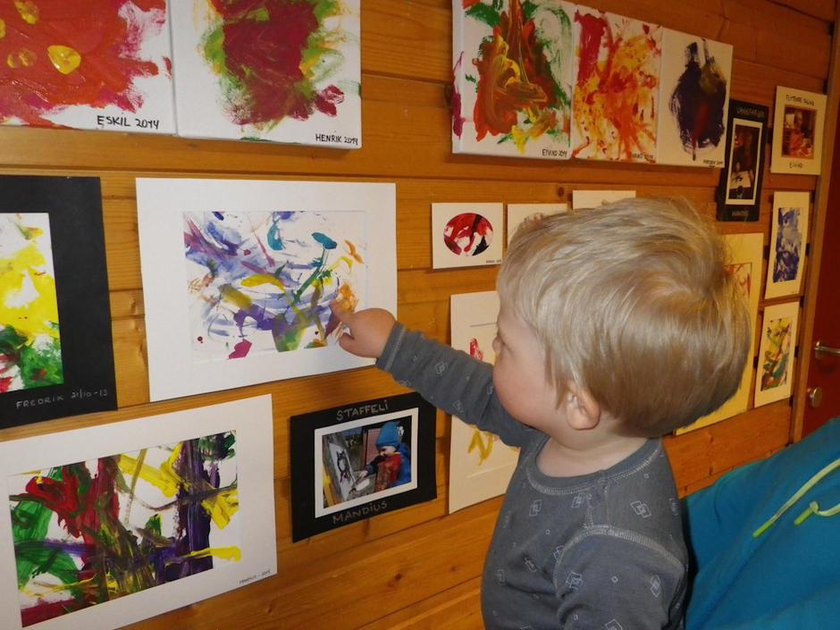 Barnas egen kunstutstilling i Borgenveien barnehage. Et barn peker på sitt bilde.