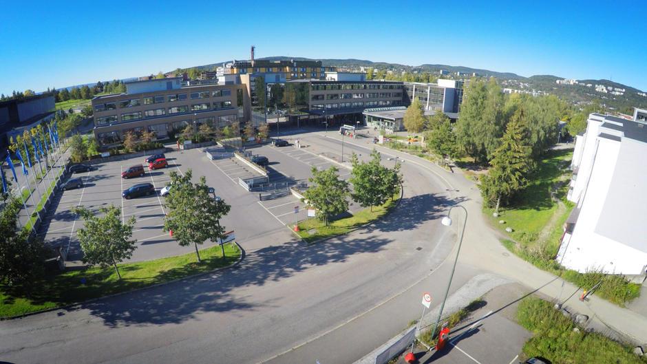 Oversiktsbilde av Trygve Lies plass på Furuset, i dag en parkeringsplass og et busstopp.
