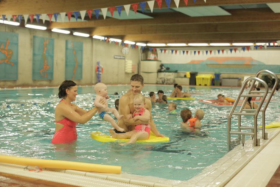 Familie koser seg i bassenget.